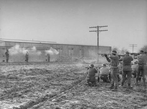 """The volley is fired and three white puffs of smoke appear against the wall of the concrete block. The initial burst killed all three almost instantaneously. The firing squad, all military police, consisted of three groups of eight men, each with one additional marksman along as a spare."""